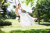 Young bride swinging in garden