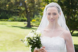 Bride smiling through veil in garden