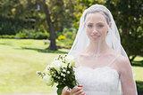 Bride smiling through veil in garden