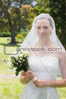Beautiful bride with flower bouquet wearing veil