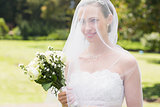 Bride looking away through veil in garden