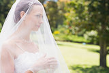 Young bride looking away through veil in garden