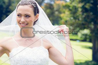 Bride unveiling self in garden
