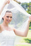 Happy beautiful bride unveiling self in garden