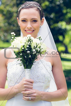 Bride smiling while holding flower bouquet in garden