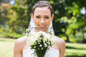 Bride with flower bouquet smiling in garden