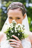 Young bride peeking over bouquet in garden