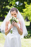 Bride smelling fresh flowers in garden