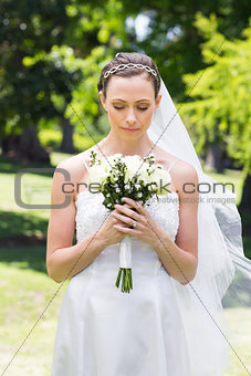 Bride holding flower bouquet in garden