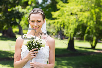 Attractive bride holding flower bouquet in garden