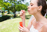 Bride blowing bubbles in garden