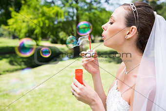 Beautiful bride blowing bubbles in garden
