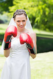 Bride wearing boxing gloves in garden
