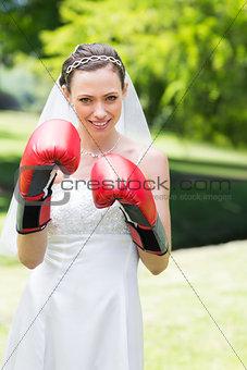 Bride wearing boxing gloves in garden