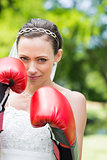 Woman in wedding dress wearing boxing gloves