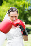 Bride with boxing gloves punching in garden