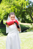 Bride with boxing gloves punching in park