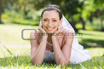 Bride in wedding gown lying on grass