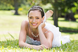 Attractive bride relaxing on grass