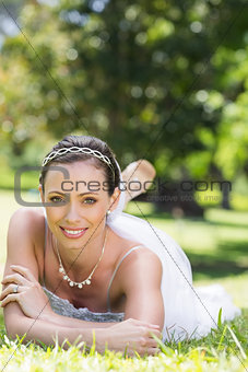 Beautiful young bride relaxing on grass