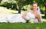Beautiful bride lying on grass in park