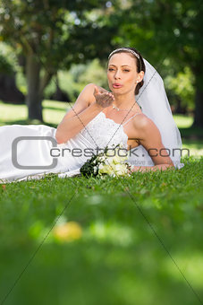 Bride blowing a kiss in park