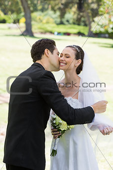 Groom kissing bride in garden