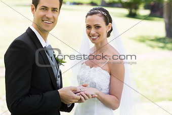 Groom placing ring on brides finger at park