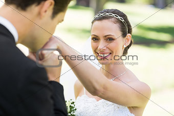 Groom kissing on hand of beautiful bride