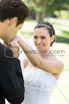 Groom kissing on hand of beautiful bride