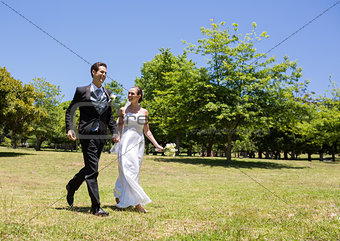 Bride and groom holding hands walking in park