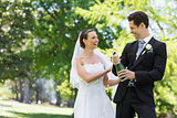 Newlywed couple opening champagne bottle