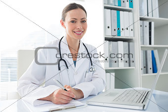 Doctor with laptop and clipboard sitting at desk