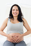 Happy pregnant woman making heart shape on belly
