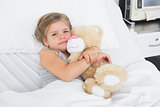 Cute girl embracing teddy bear in hospital bed