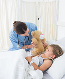 Doctor with teddy bear entertaining sick girl
