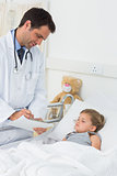 Doctor writing on clipboard while attending ill girl