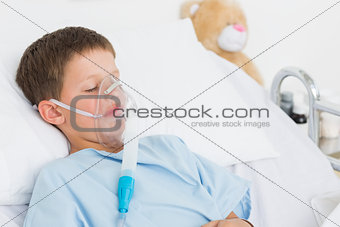 Boy with oxygen mask in bed