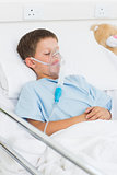 Boy with oxygen mask in hospital ward