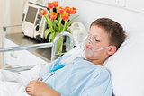 Boy wearing oxygen mask in hospital