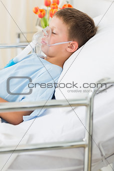 Boy wearing oxygen mask in bed