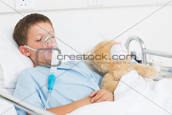 Boy wearing oxygen mask sleeping beside teddy bear