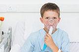 Boy wearing oxygen mask in hospital bed