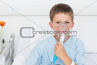 Boy wearing oxygen mask in hospital bed