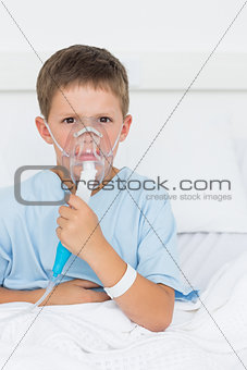 Boy wearing oxygen mask in hospital ward