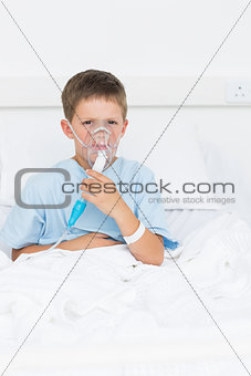 Boy on bed with oxygen mask in hospital