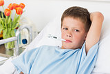 Boy in hospital bed with thermometer
