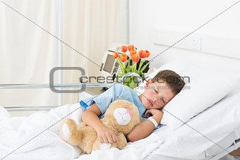 Boy sleeping with teddy bear in hospital