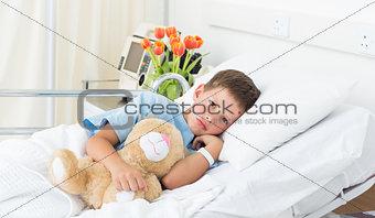 Boy lying with teddy bear in hospital