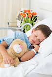 Boy with teddy bear sleeping in hospital